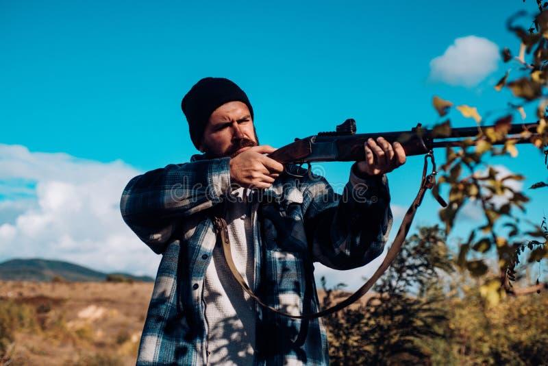 Bearded hunter man holding gun and walking in forest. Hunter with shotgun gun on hunt. Big game. royalty free stock image