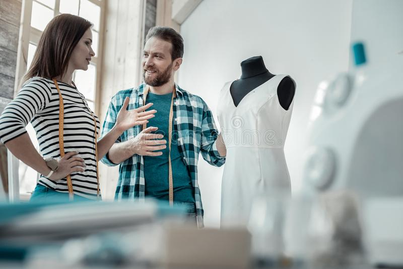 Bearded husband giving his piece of advice to his wife. Piece of advice. Bearded husband giving his piece of advice to his wife designing bridal dress royalty free stock photo
