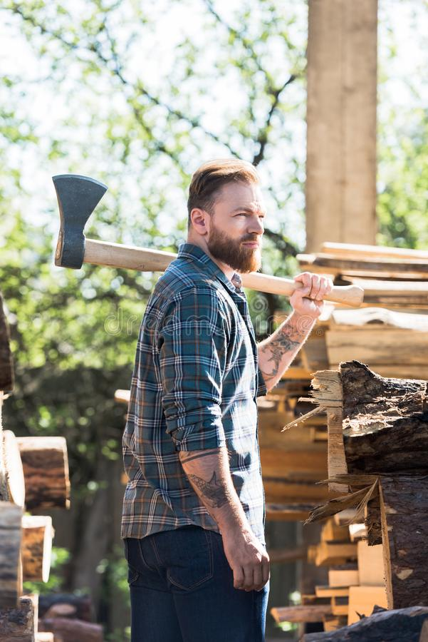bearded lumberjack in checkered shirt with tattooed hand holding axe on shoulder stock images