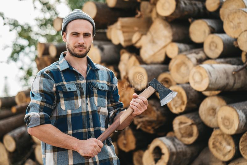 Bearded lumberjack wearing plaid shirt hold ax in hand stock photos