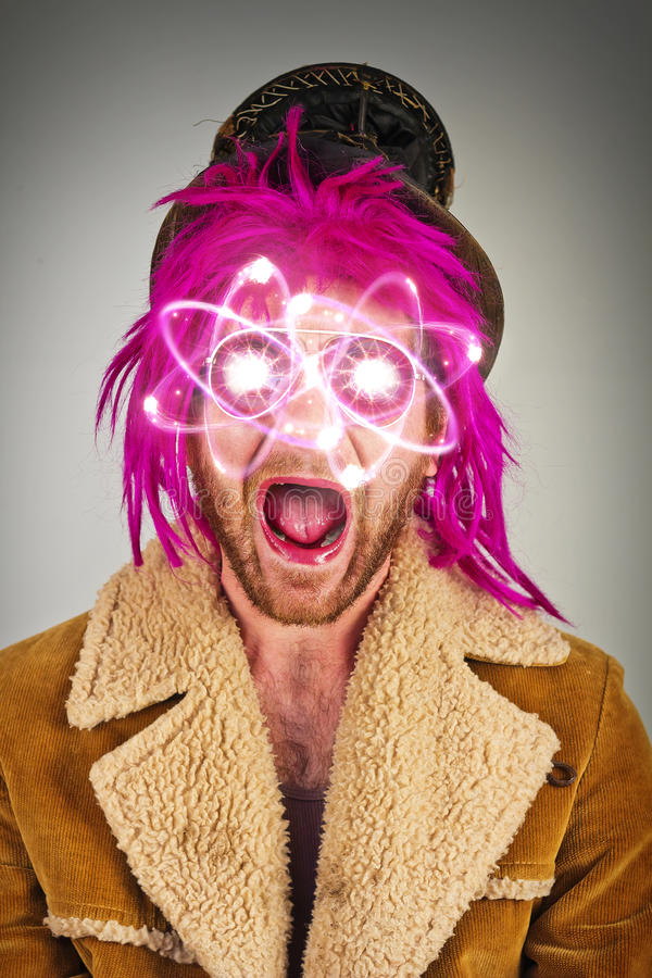 Bearded Lunatic Atomic Energy. Pink haired bearded lunatic with atomic particle sunglasses stock photography