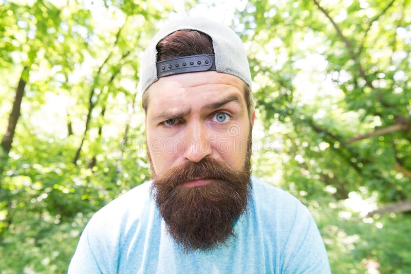 Bearded macho. Hipster with long beard emotional face close up nature background. Brutal male leisure. Summer travel royalty free stock image