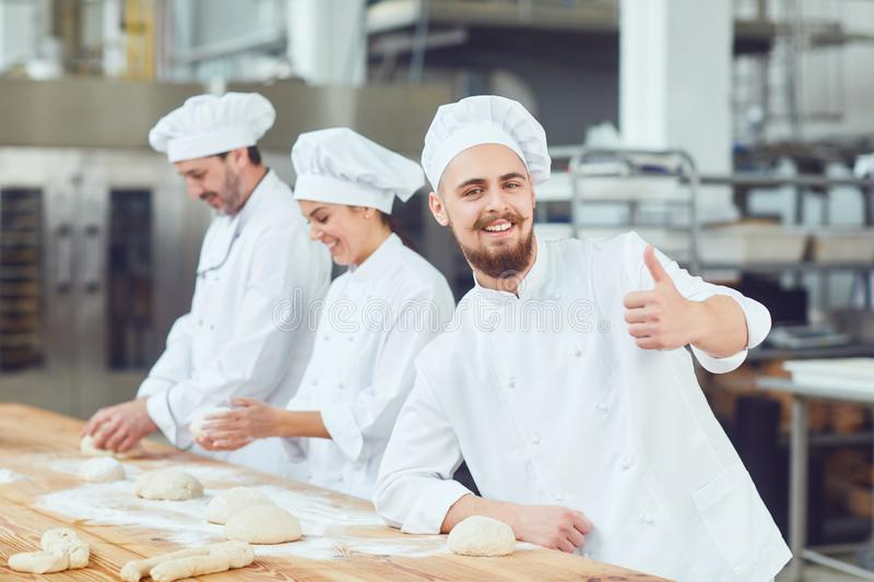 Bearded male baker at the bakery. Bearded male baker shows thumb up at the bakery stock photography