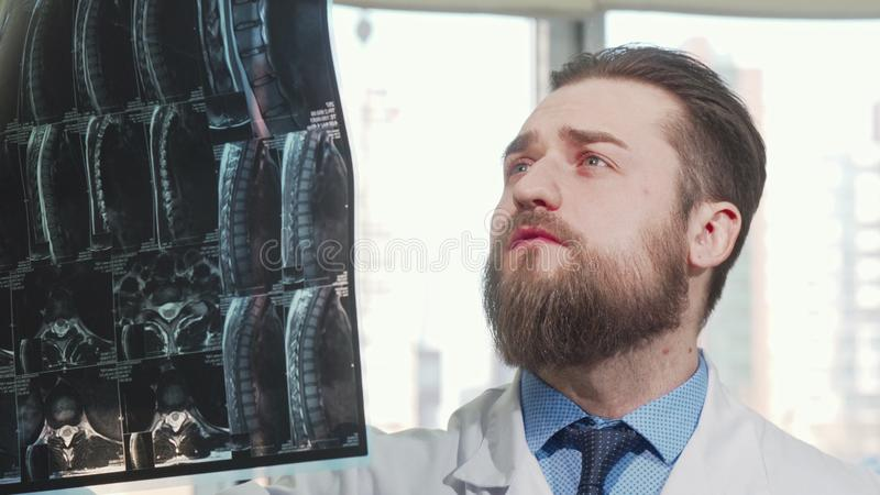 Bearded male doctor examining mri scan of his patient stock photo