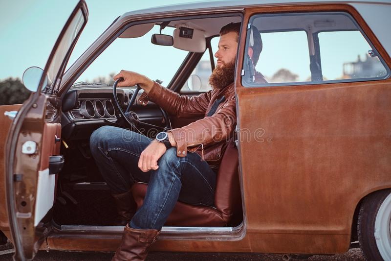 Bearded male dressed in brown leather jacket sits behind the wheel of a tuned retro car with open door. Stylish bearded male dressed in brown leather jacket royalty free stock photo