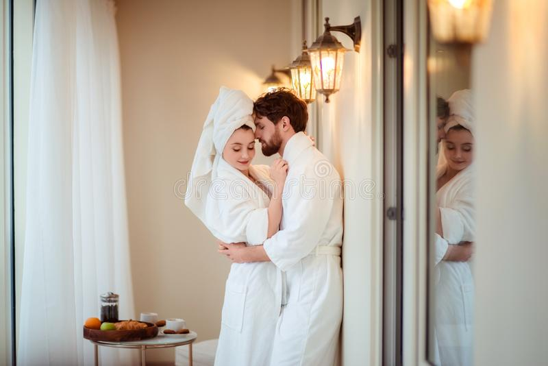 Bearded male and his wife wears white bathrobes and towel on head, hug each other, feel relaxed after taking bath in stock photography