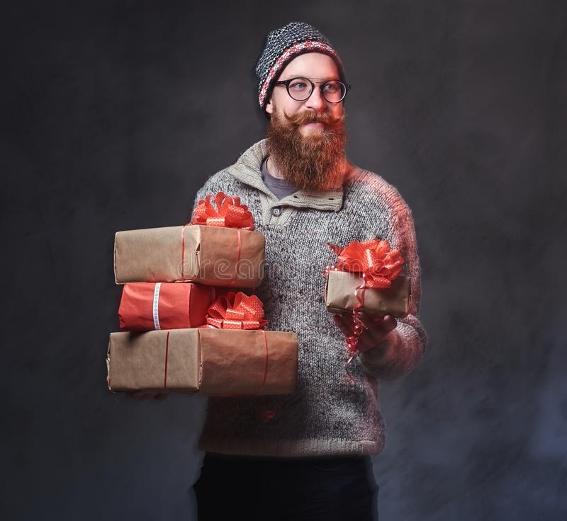 Bearded male holds Christmas gifts. stock photo