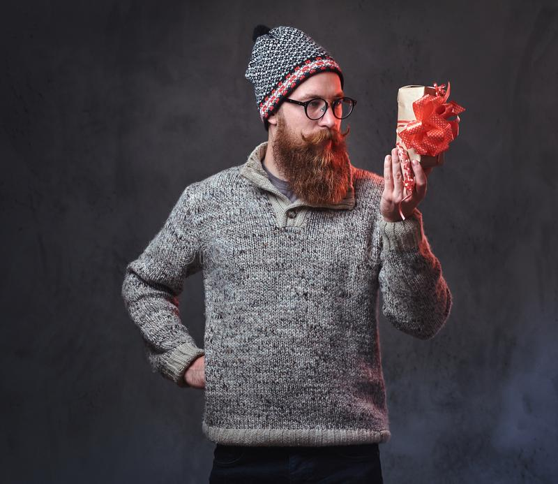 Bearded male holds Christmas gifts. royalty free stock images