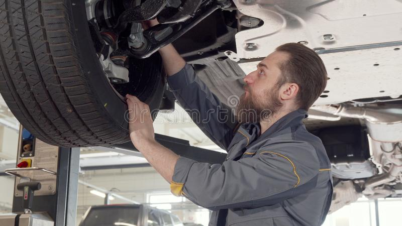 Bearded male mechanic checking wheels of a car on a lift at the garage. Professional auto technician working with lifted car, examining wheels. Safety stock photography