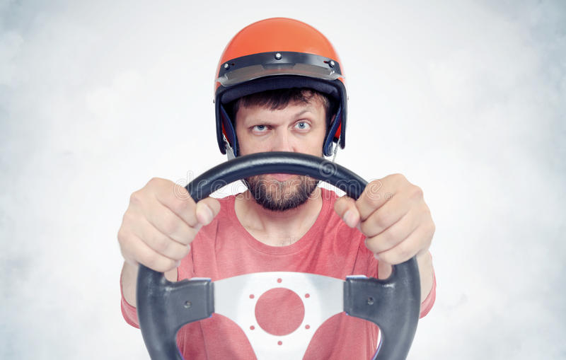 Bearded male in red helmet with steering wheel. car driver concept.  stock photo