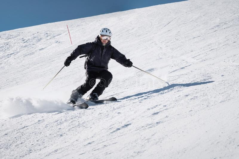 Bearded male skier in a helmet and a ski mask rides on a slope at speed and brakes with snow powder on skis against the royalty free stock photography