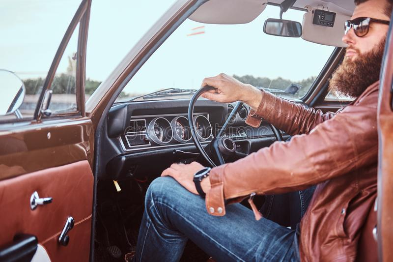Bearded male in sunglasses dressed in brown leather jacket sits behind the wheel of a tuned retro car with open door. stock image