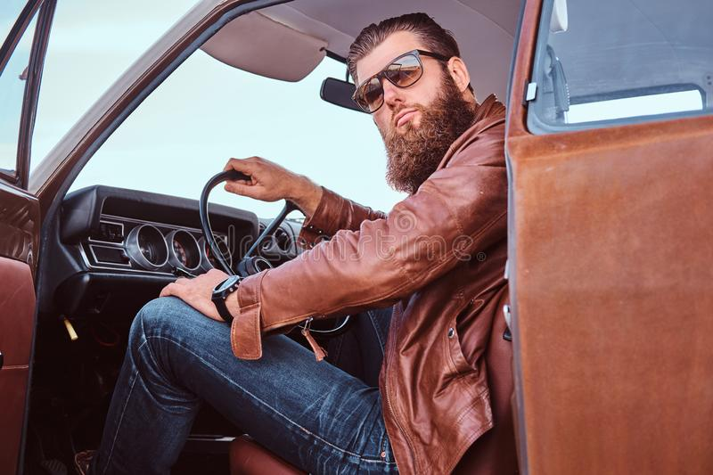 Bearded male in sunglasses dressed in brown leather jacket sits behind the wheel of a tuned retro car with open door. royalty free stock image