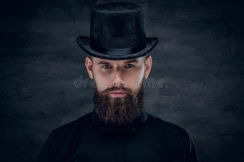 Bearded male with tattoo on his neck and top hat cylinder on hea royalty free stock images