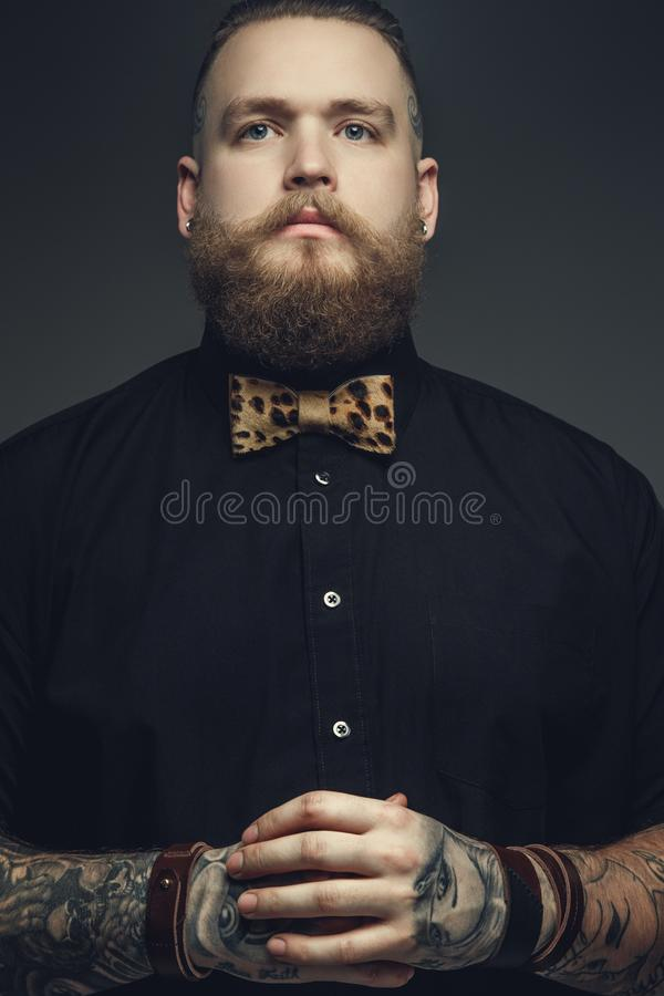 Bearded male with tattooes on his arms. stock photography