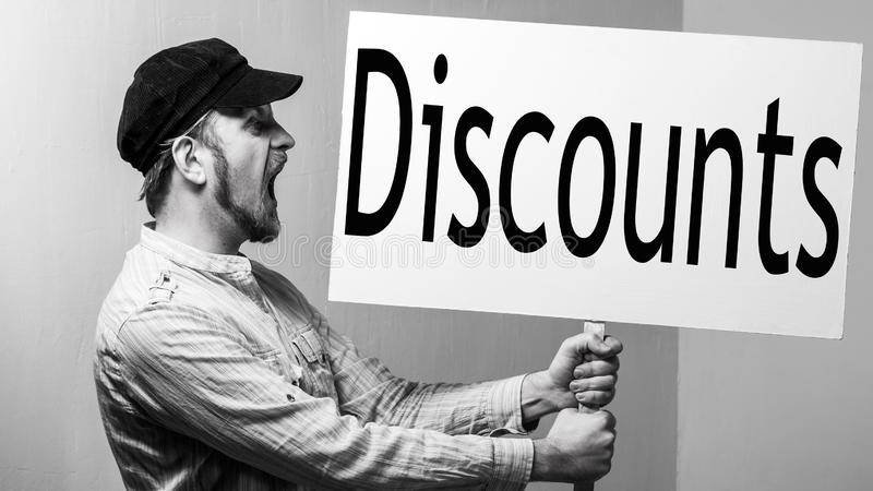 Bearded male worker in a cap shouts with a poster in his hands. Inscription discounts. Shopping concept stock photos