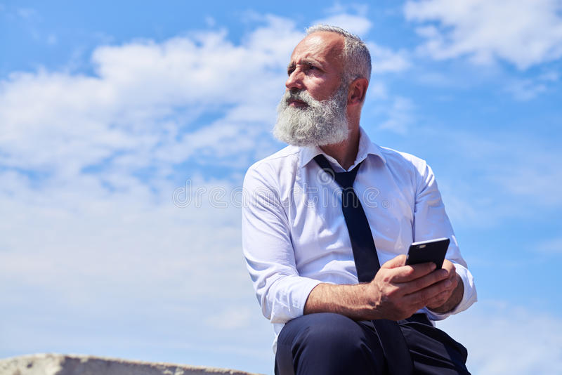 Bearded man against blue sky royalty free stock photo