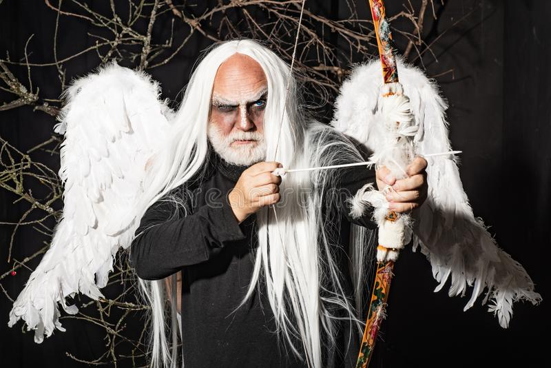 Bearded Man with angel wings. Senior man posing with angel wings. Tree spirit and fantasy concept. Ancient alchemy. Vampire man with white eyes stock image
