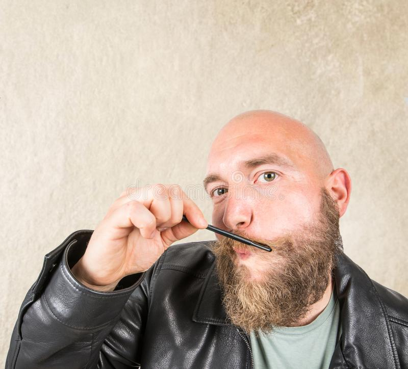 Bearded man arranging his beard with comb. A bearded man arranging his beard with comb stock photography
