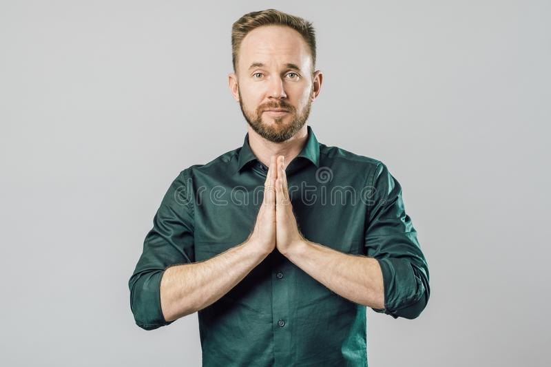 Bearded man asking for forgiveness isolated on gray background royalty free stock image