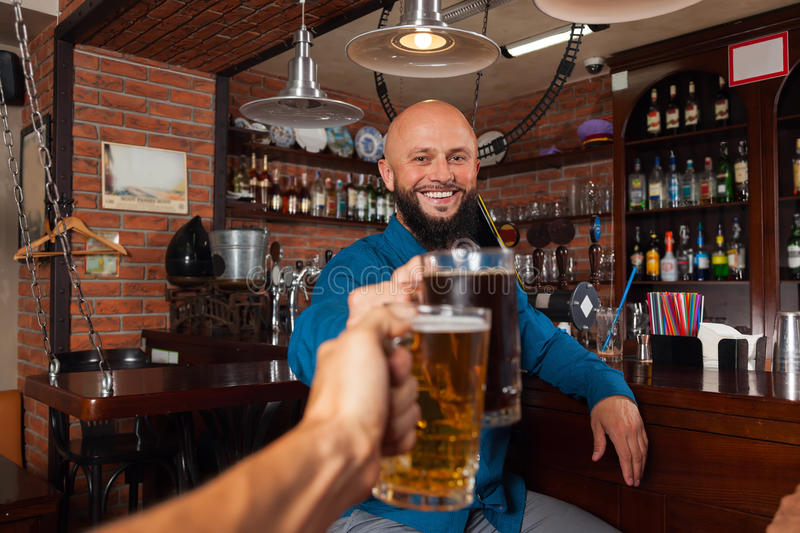 Bearded Man In Bar Clink Glasses Toasting, Drinking Beer Hold Mugs, Cheerful Friends Meeting royalty free stock photos