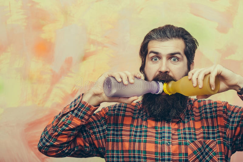 Bearded man with beard drinking from two plastic bottles royalty free stock photography