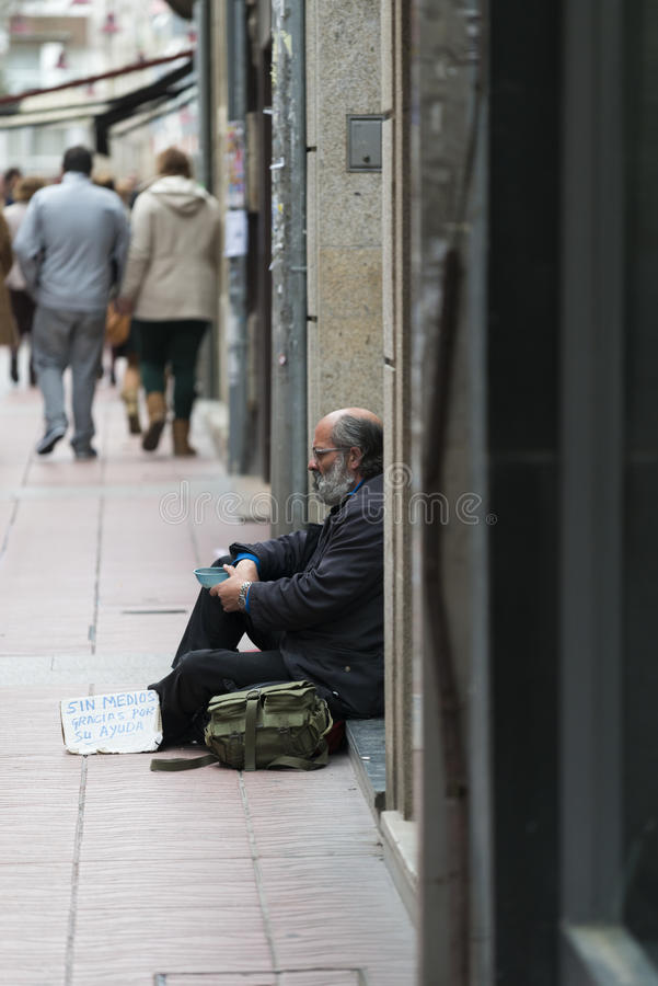 A bearded man begging. PONTEVEDRA, SPAIN - MARCH 29, 2015: A bearded man sitting in a doorway of a house, begging to people passing by his side royalty free stock photography