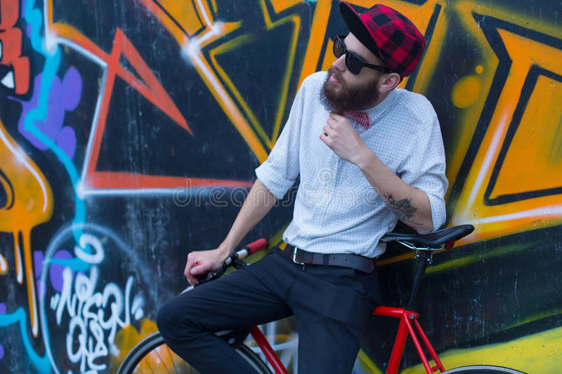Bearded man with bicycle. Young hipster man with a bike posing near a wall full of graffiti stock photo
