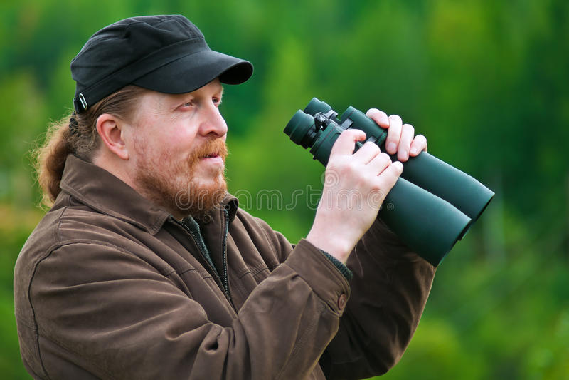 A bearded man with binoculars. stock photography