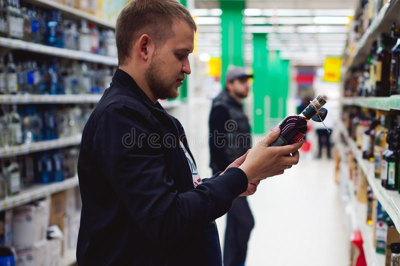 bearded man, In a black jacket, stopped to make my choice in store window, holds a bottle of strong alcohol stock photo