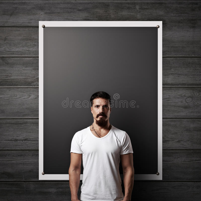 Bearded man and black poster on a wood wall stock photography