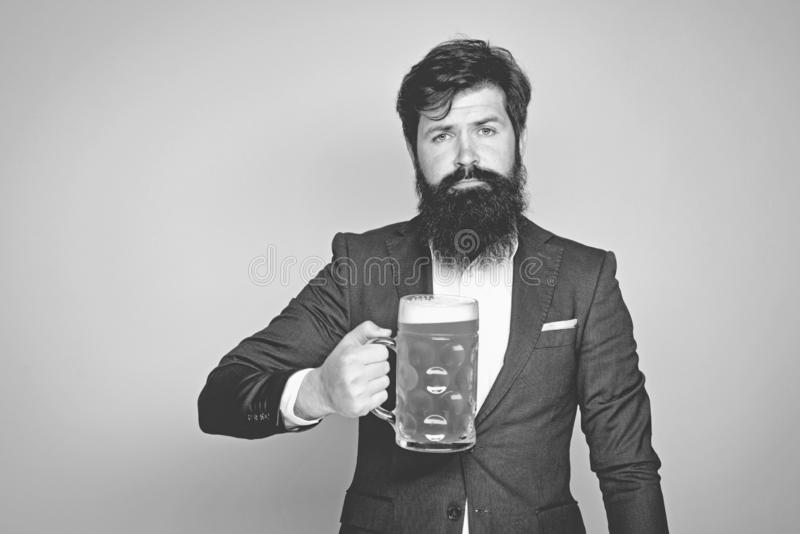 Bearded man in black suit with a glass of beer. Happy elegant man drinking beer. Beer pubs and bars. Bearded man. Drinking lager beer royalty free stock images
