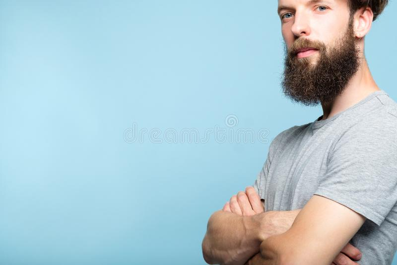 Power leader dominance authoritative man fold arms. Bearded man on blue background expressing power force leadership supremacy and dominance. confident and royalty free stock photo
