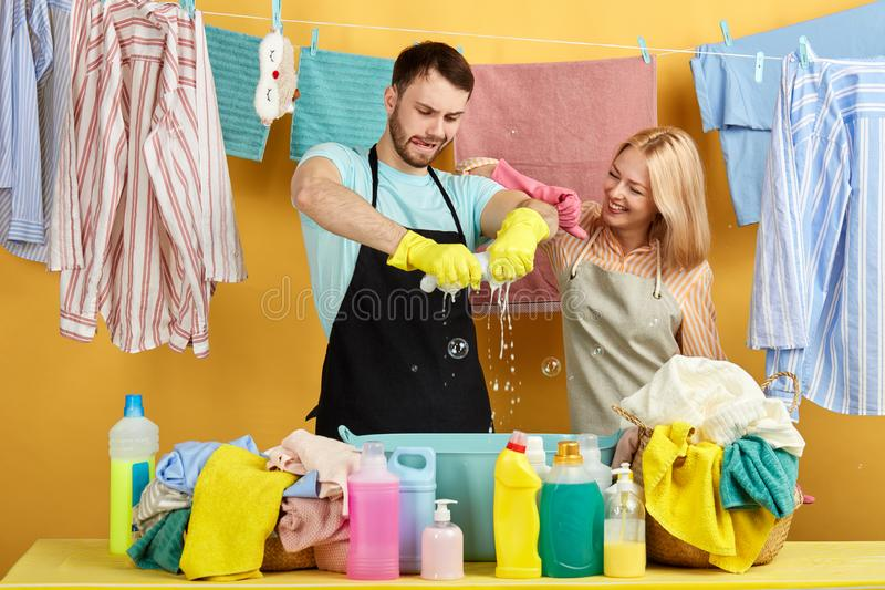 Bearded man in blue T-shirt nad black apron concentrated on wringing out wet clothes. Hardworking men in blue T-shirt nad black apron concentrated on wringing stock photos