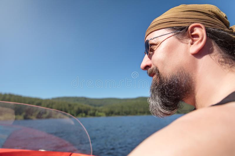 Bearded Man is boating on a lake, concept travel and holiday trip. Copyspace royalty free stock photo