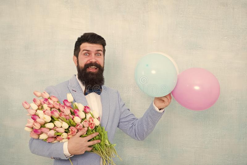 Bearded man in bow tie with tulip flowers. love date with flowers. Happy Birthday. womens day. Formal mature businessman stock image
