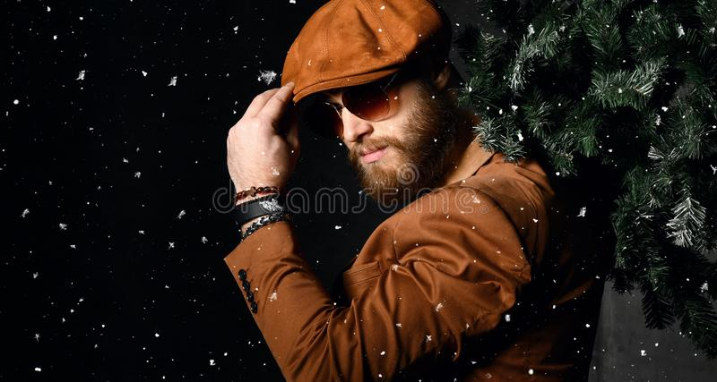 Bearded man in brown leather jacket and cap hold Christmas tree under snow stock photography