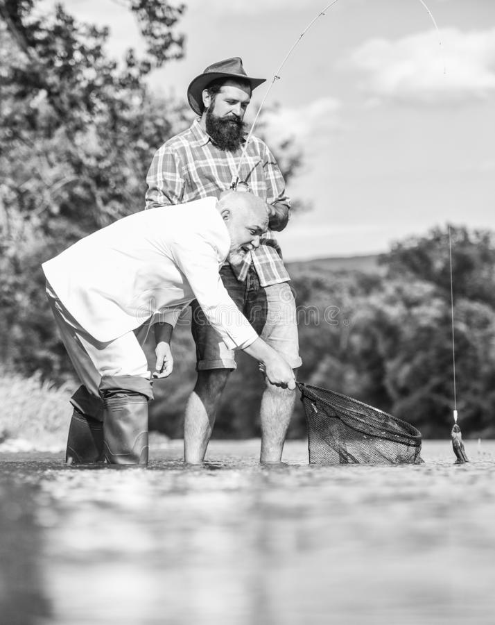Bearded man and brutal hipster fishing. Fishing team. Friends catching fish. Peace of mind and tranquility. Freshwater royalty free stock photography