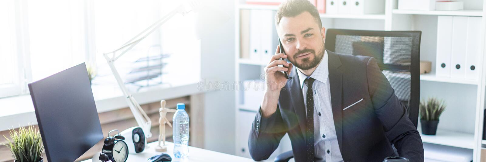 A man is sitting at the desk at the office, talking on the phone and looking straight. A bearded man with a business suit is working in a bright office. photo stock image