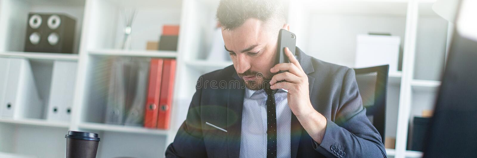 A man is sitting in the office at the table, talking on the phone and flipping through documents. A bearded man with a business suit is working in a bright royalty free stock photo