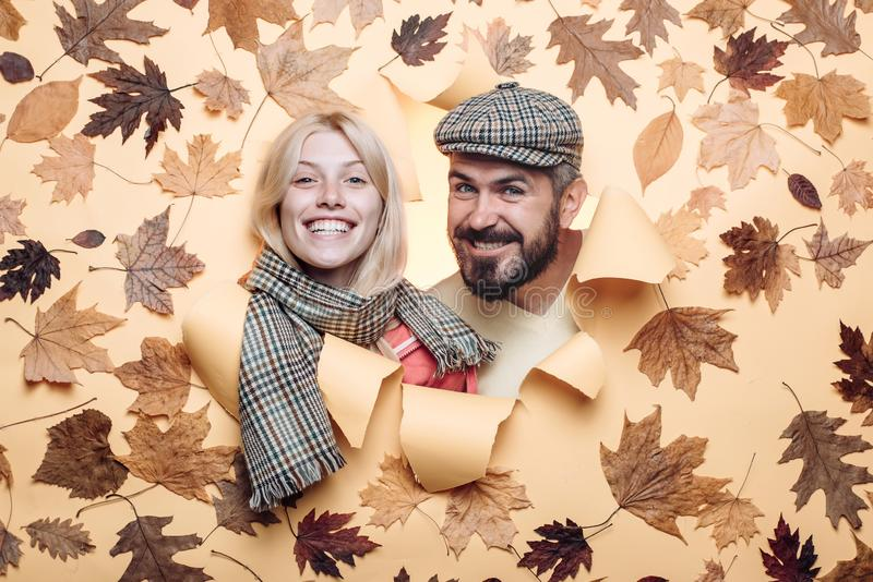 Bearded man in cap and blond girl with scarf are happy with autumn sales. Romantic couple wearing pullover on autumn stock image