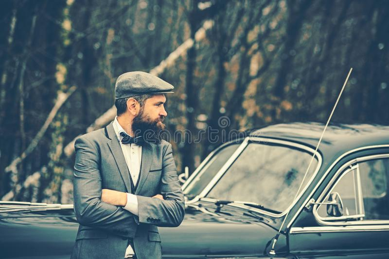 Bearded man in car. Escort man or security guard. Retro collection car and auto repair by mechanic driver. Call boy in stock photos