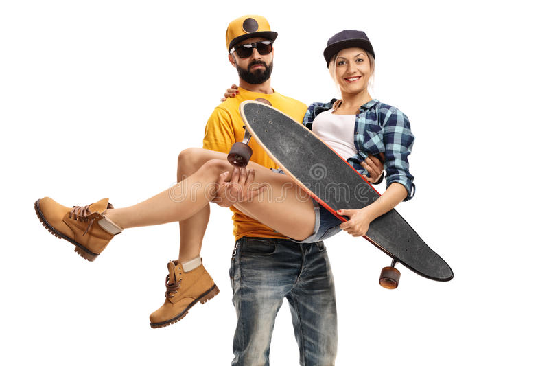 Bearded man carrying a female skater with a longboard royalty free stock image