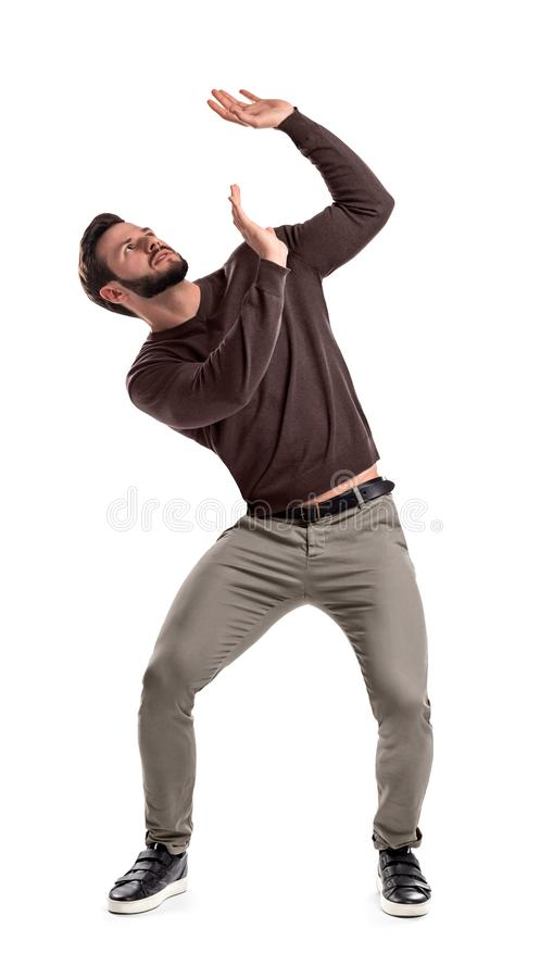 A bearded man in casual garb stands protecting himself with outstretched hands from something getting to him from above. Dangerous position. Big problems royalty free stock image