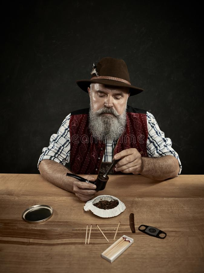 Bearded man clogs the tobacco in pipe. The senior bearded man sitting at table and clogging the tobacco in pipe. The male hands close up. Bavaria. a man dressed stock photo