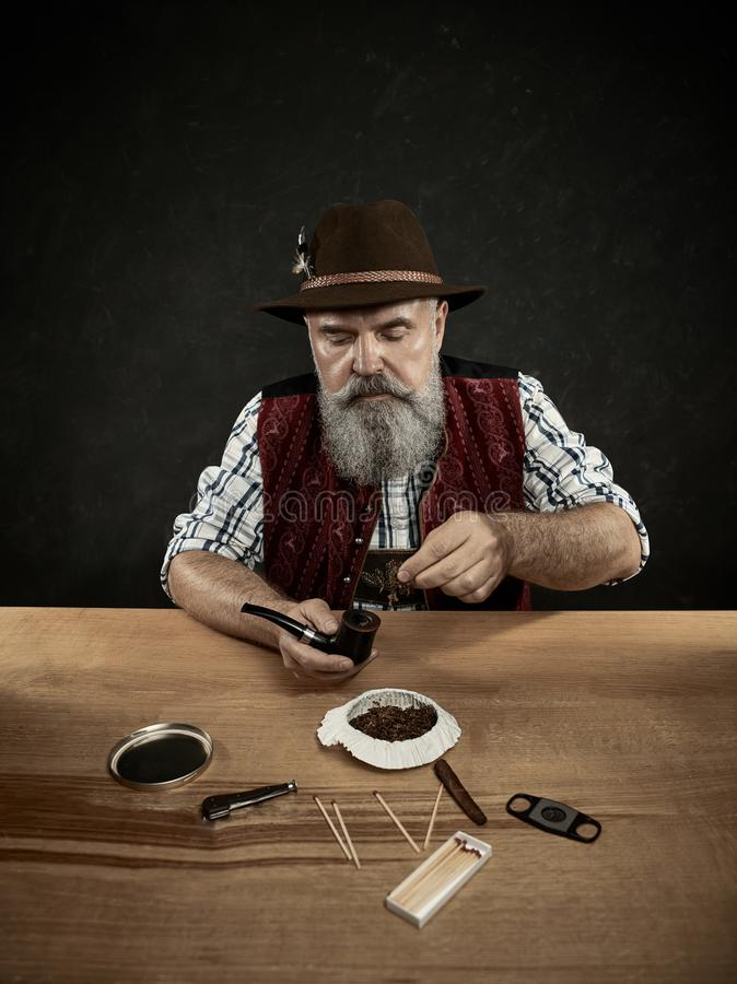 Bearded man clogs the tobacco in pipe. The senior bearded man sitting at table and clogging the tobacco in pipe. The male hands close up. Bavaria. a man dressed stock images
