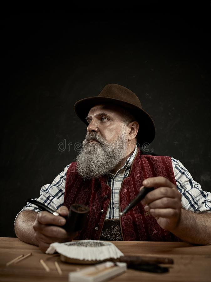 Bearded man clogs the tobacco in pipe. The senior bearded man sitting at table and clogging the tobacco in pipe. The male hands close up. Bavaria. a man dressed royalty free stock photo