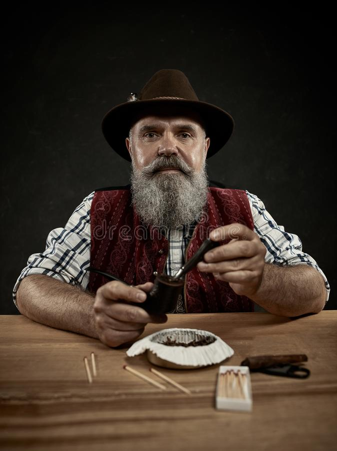Bearded man clogs the tobacco in pipe. The senior bearded man sitting at table and clogging the tobacco in pipe. The male hands close up. Bavaria. a man dressed stock image