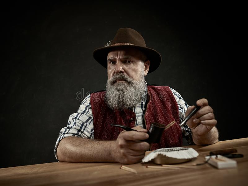 Bearded man clogs the tobacco in pipe. The senior bearded man sitting at table and clogging the tobacco in pipe. The male hands close up. Bavaria. a man dressed stock photos