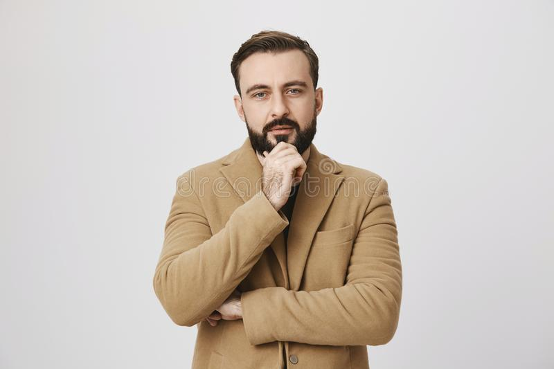 Bearded man in coat looking interested in something holding his hand on chin looking at camera over white background stock images